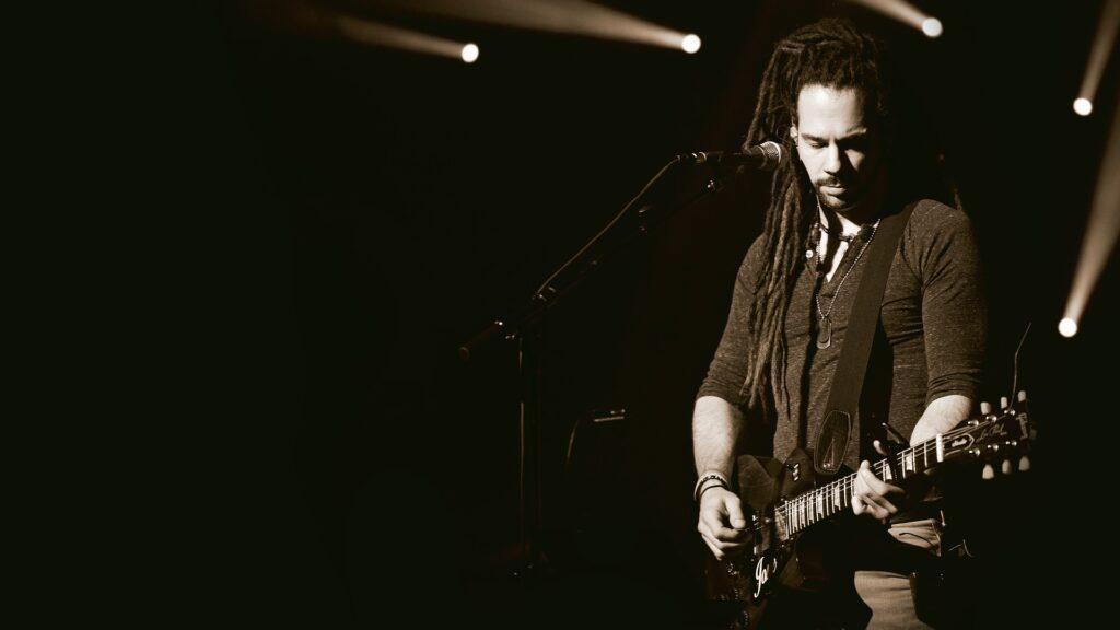 Dark sepia man playing guitar on stage