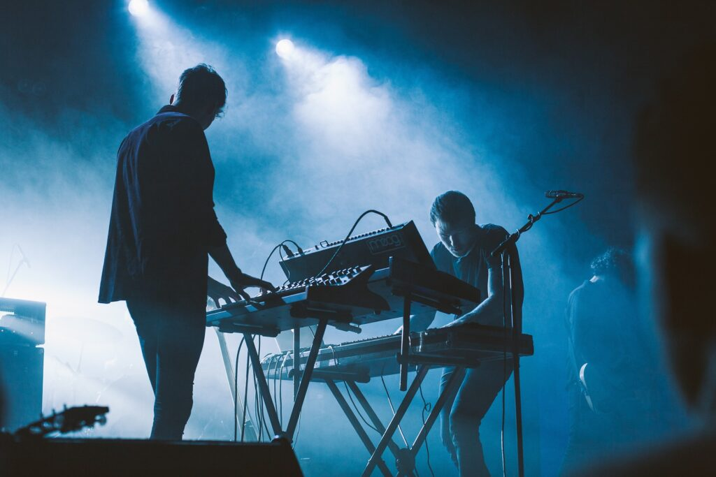 two people playing keyboards on stage with blue lighting