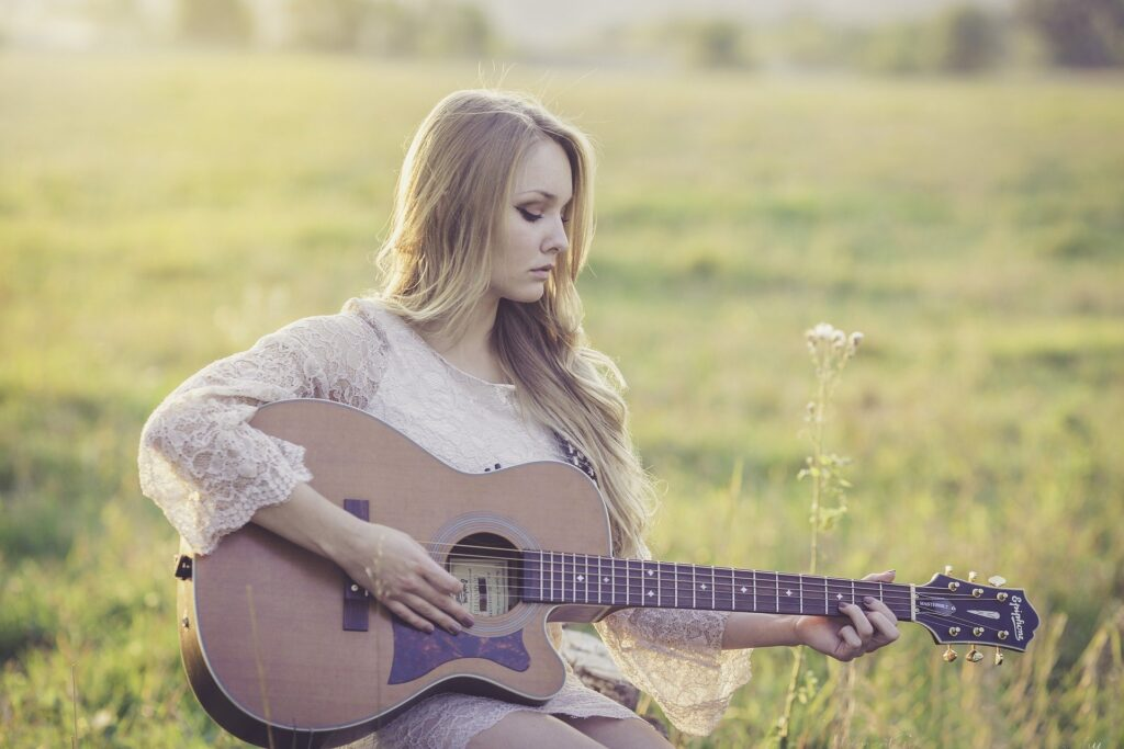 Woman holiding guitar in field