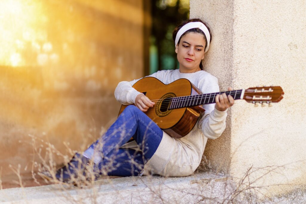 woman in white with scarf playing acoustic guitar