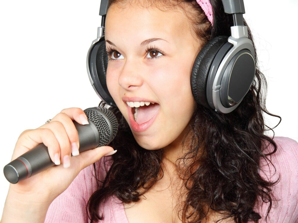 girl in pink singing into mic with big headphones on