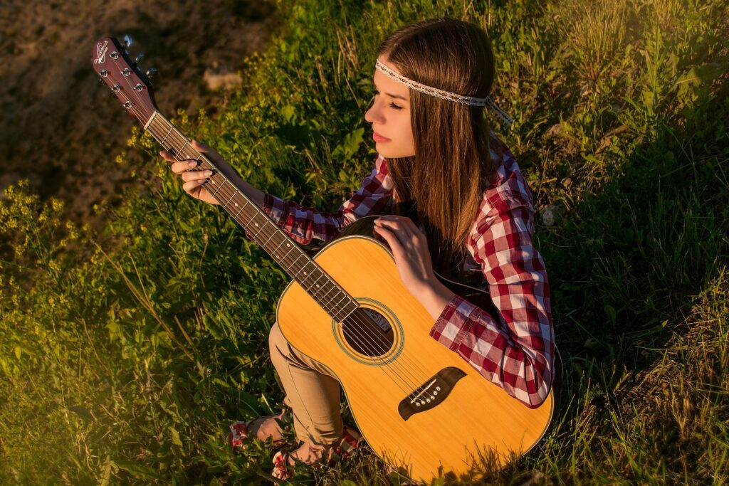 hippie girl in field with acoustic guitar