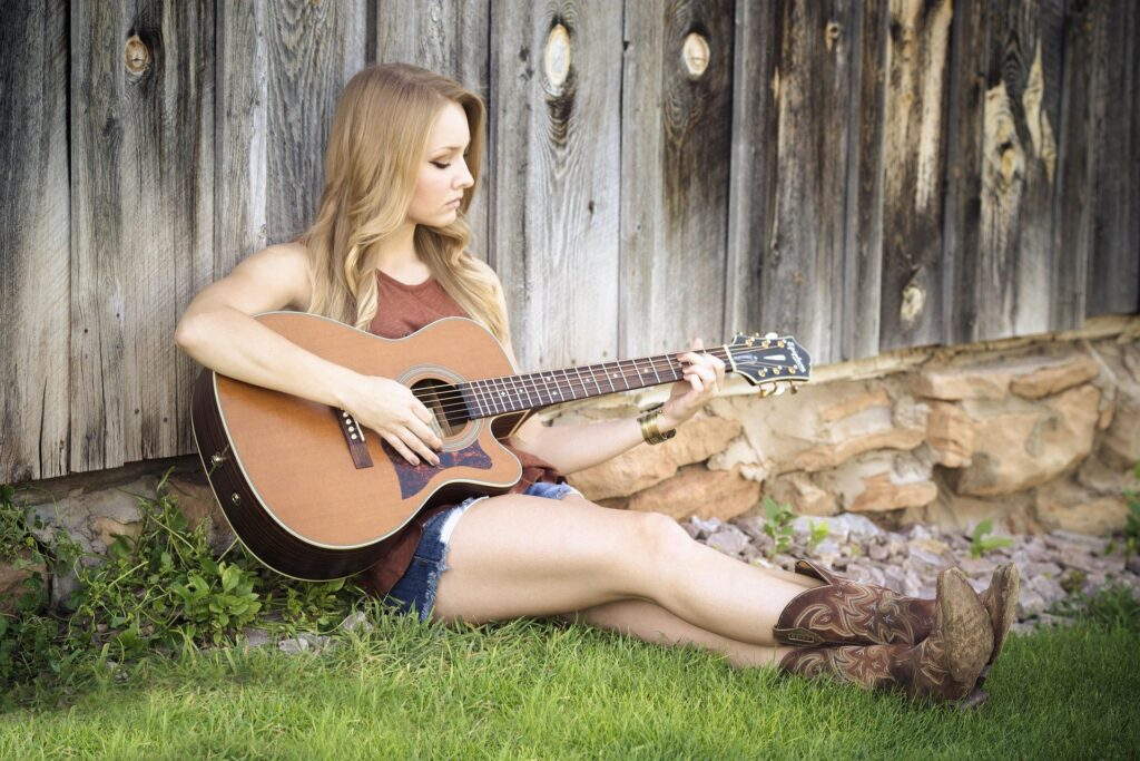 blond girl playing guitar in front of fence