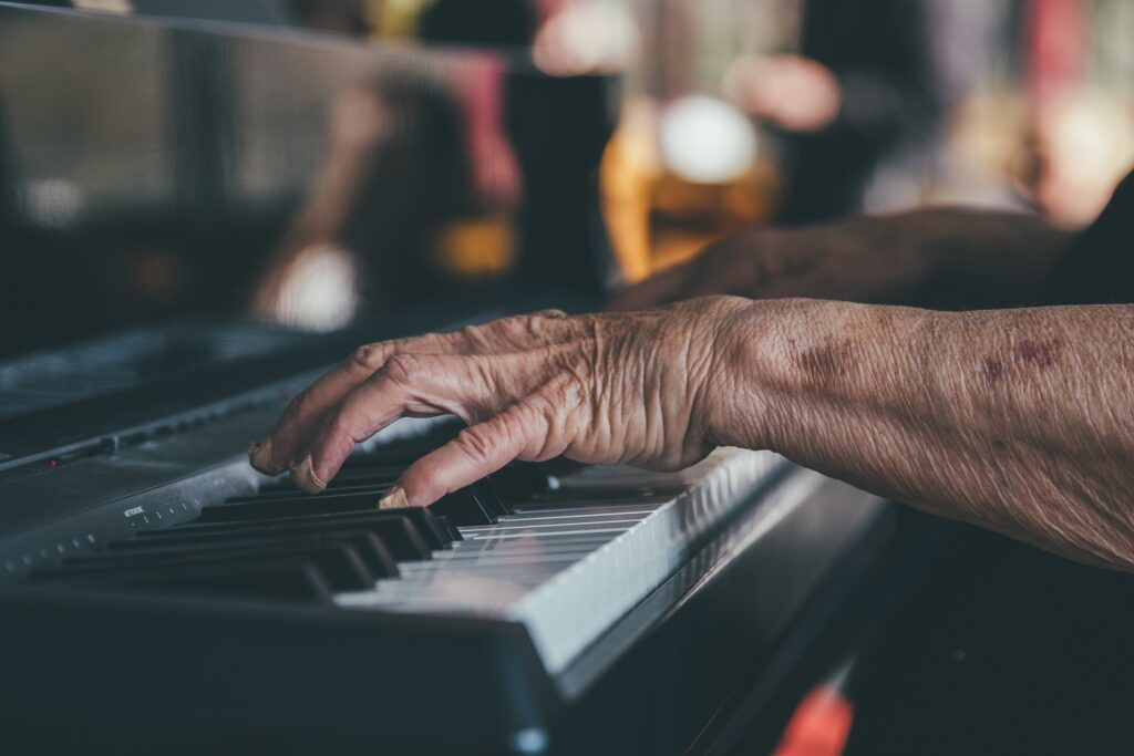 older hands playing on a keyboard