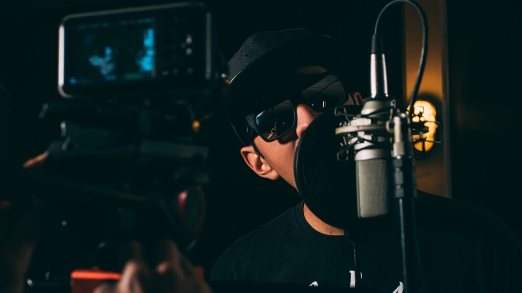 man in all black with hat and sunglasses singing into studio mic
