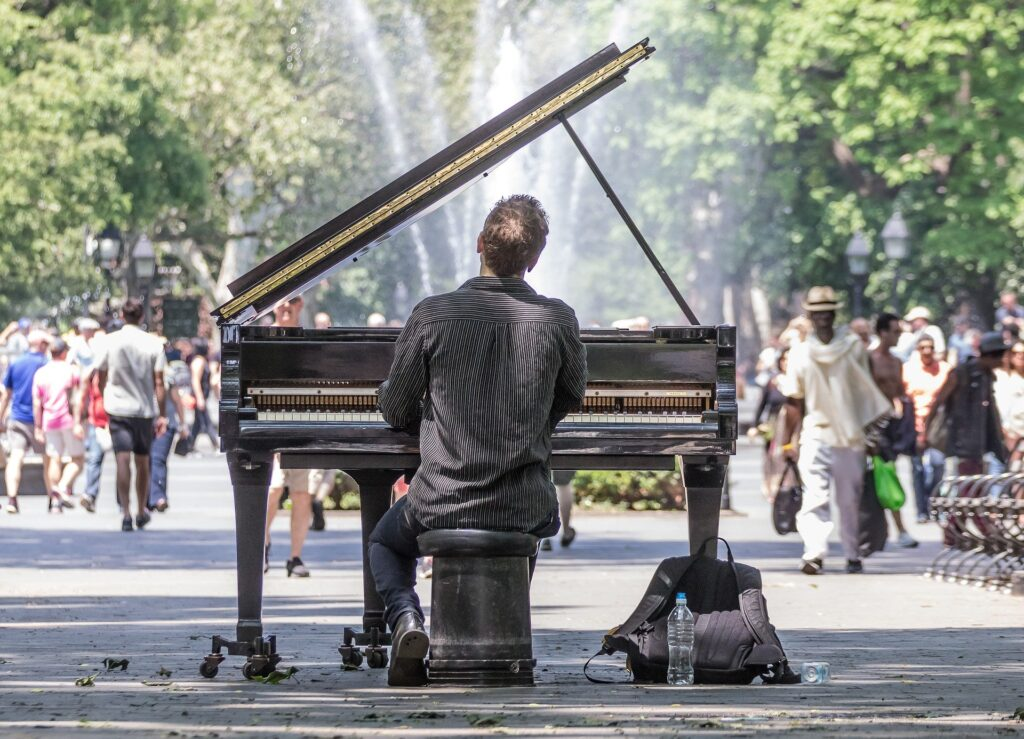 man playing piano in a park in front of a fountain