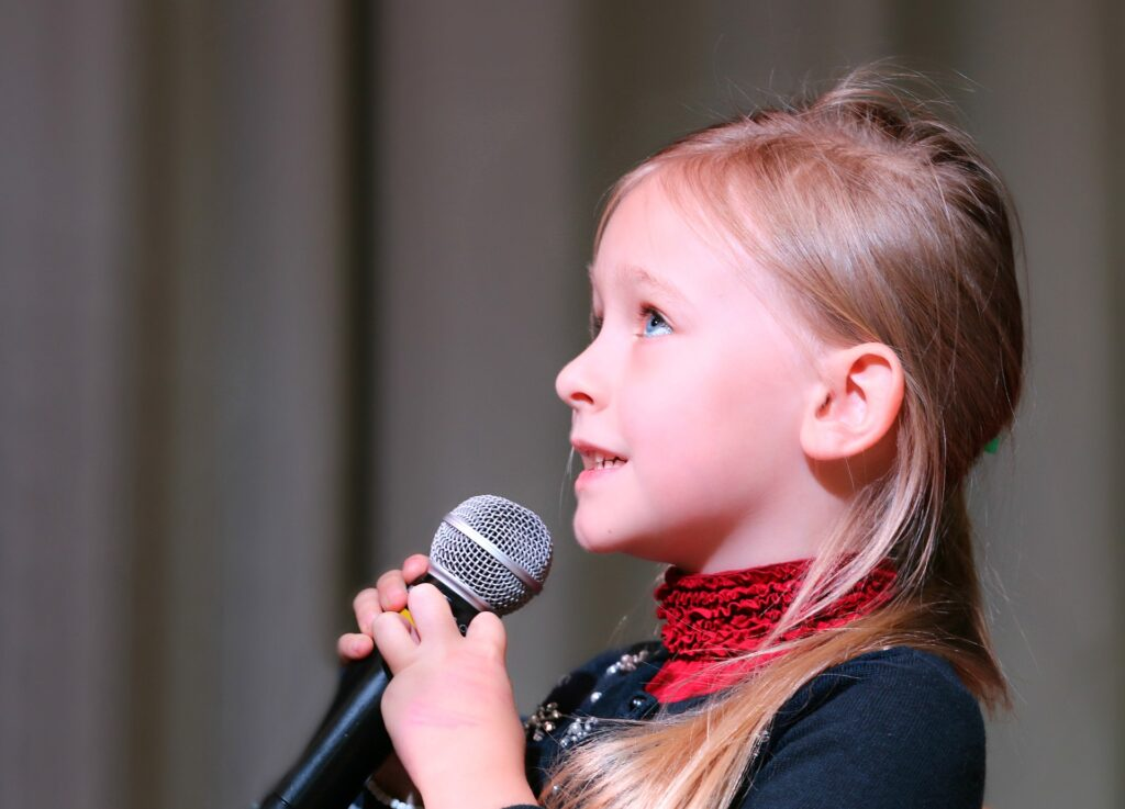 young girl singing under stage lighting