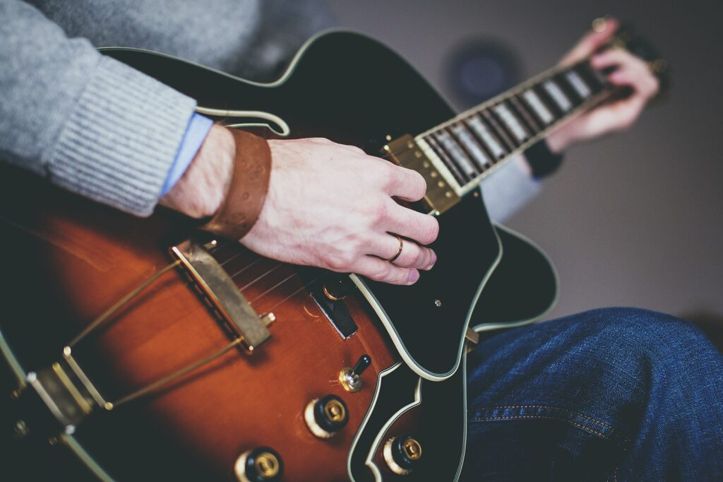 hand with ring and braclet playing an electric guitar