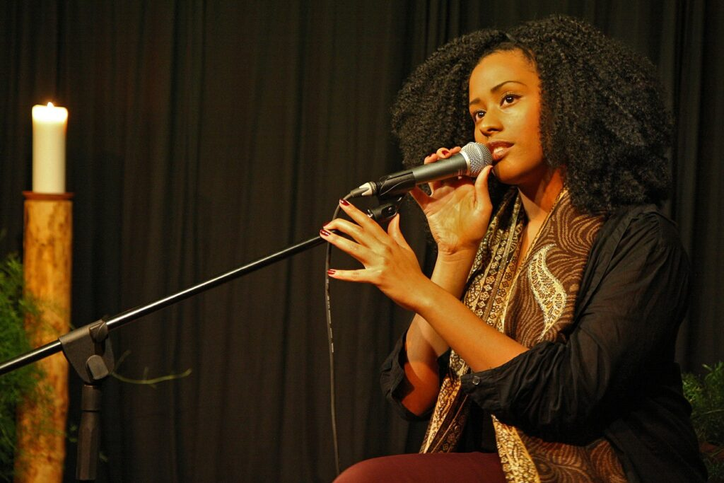woman in scarf singing expressivly into mic