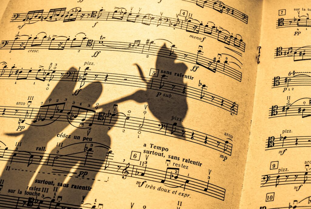 sheet music with shadow of hand holding a flower across it