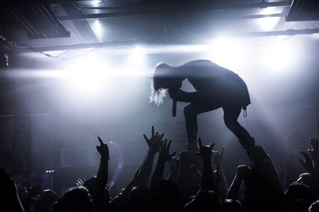 silouette of person singing on stage with crowd throwing their hands in the air