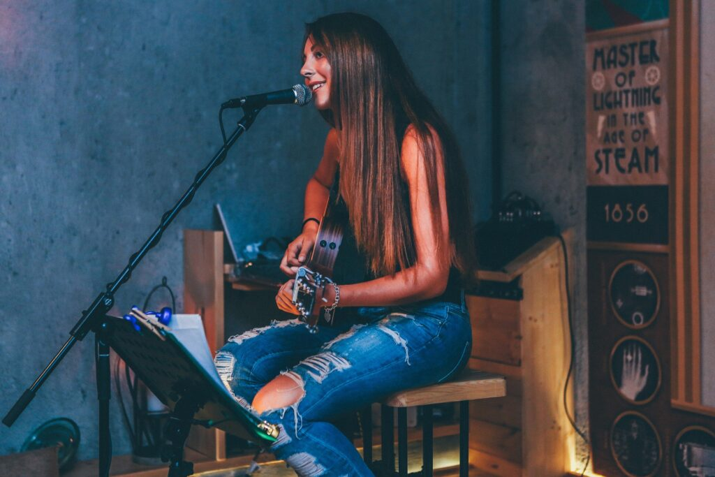 girl playing guitar and singing on a small stage