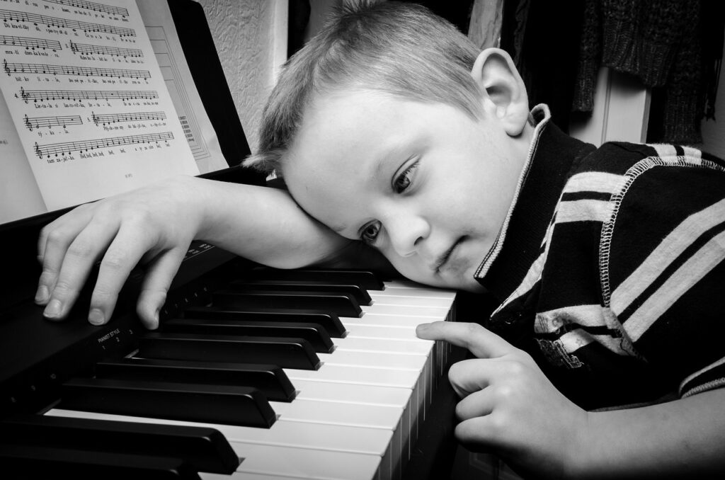 bored child laying across keyboard and playing single note
