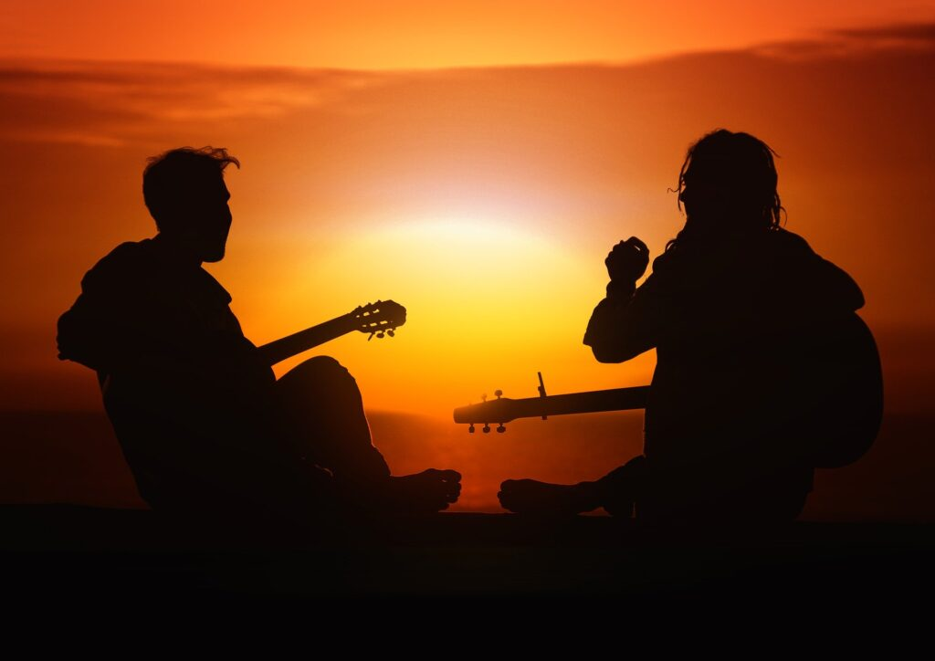 two people playing guitar at sunset