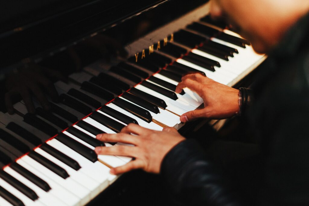 man playing the piano in black shirt