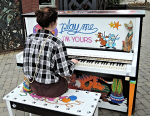 "girl in plaid shirt playing colorfully painted piano with ""play me, I'm yours"" written across it"