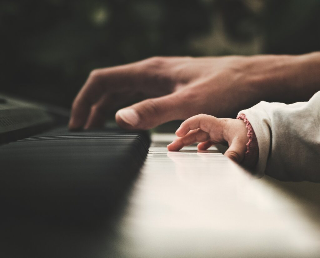 mother and child's hands on piano keys