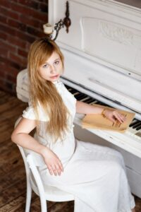 woman in white dress looking up from piano at camera
