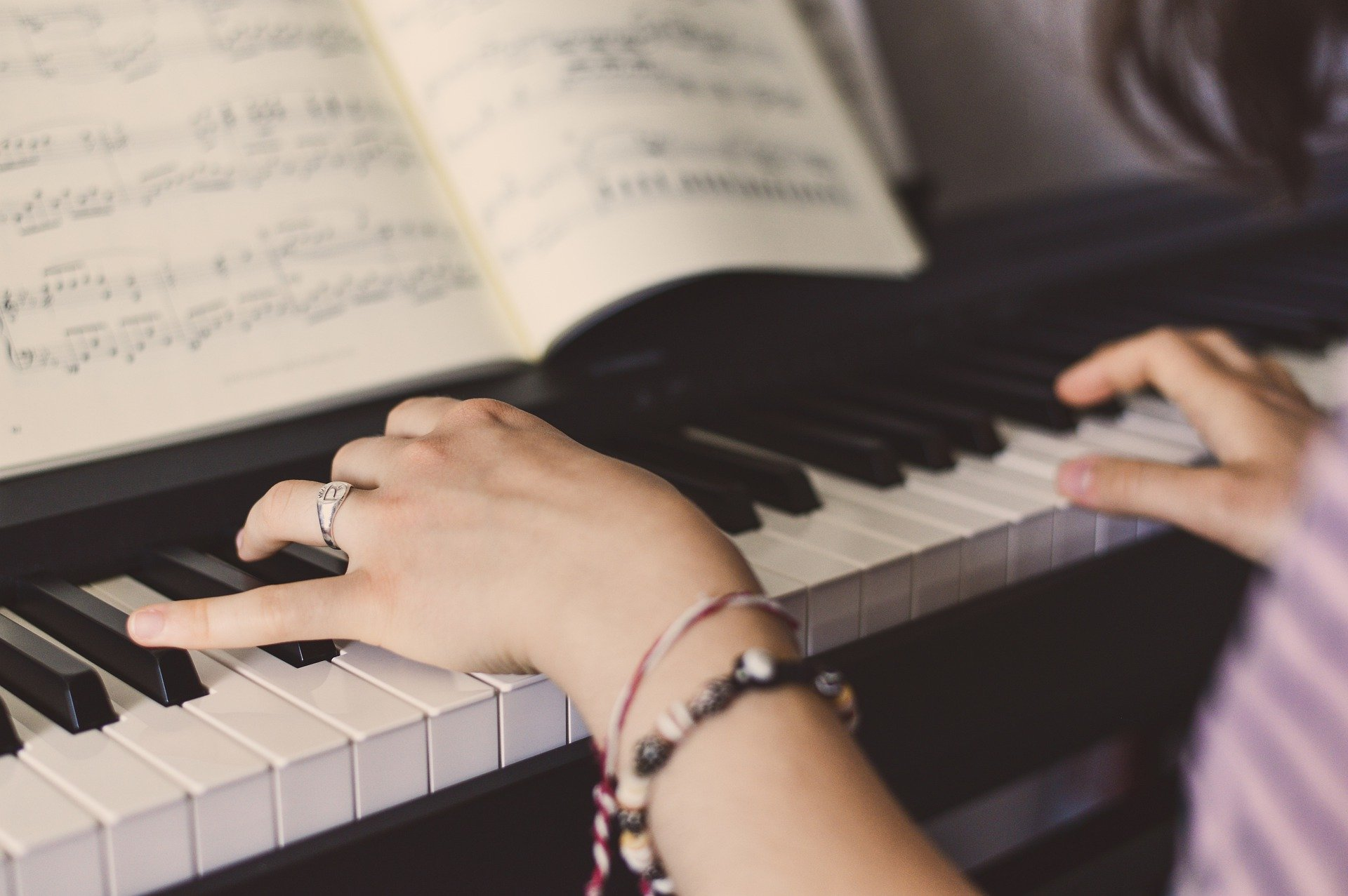 girls hands playing a piano with sheet music