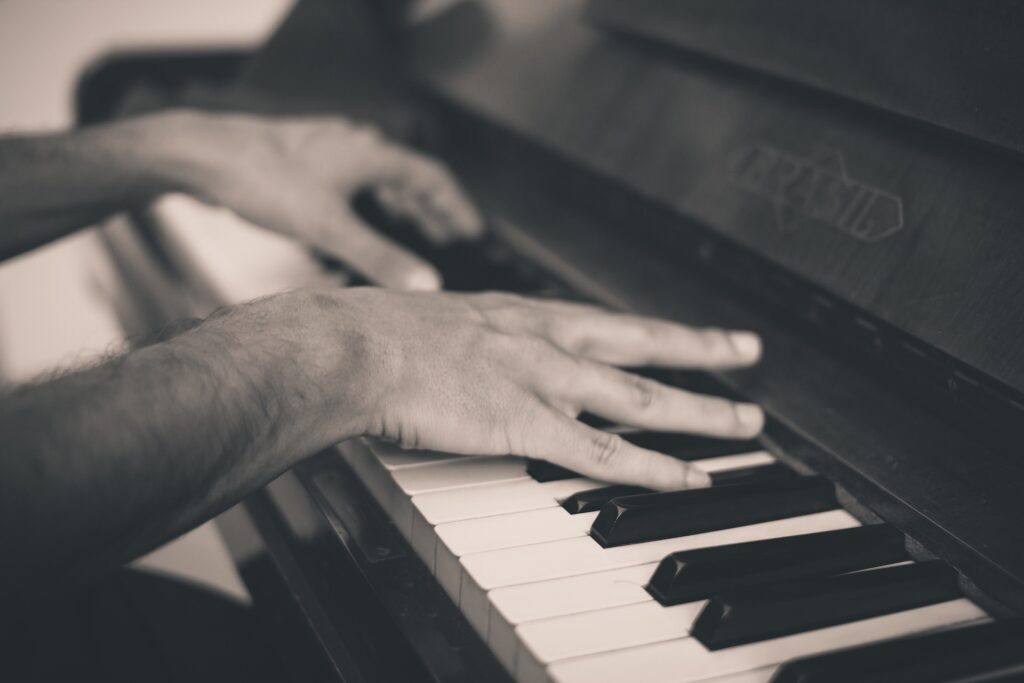 greyscale hands playing a piano