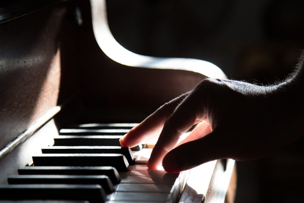 single hand playing piano keys in sunlight and shadow