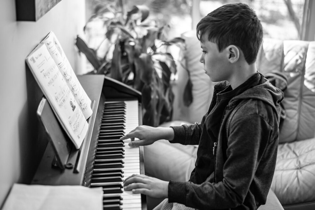 kid playing piano with sheet music black and white