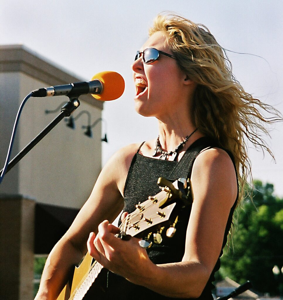 young rocker girl screaming into mic with guitar