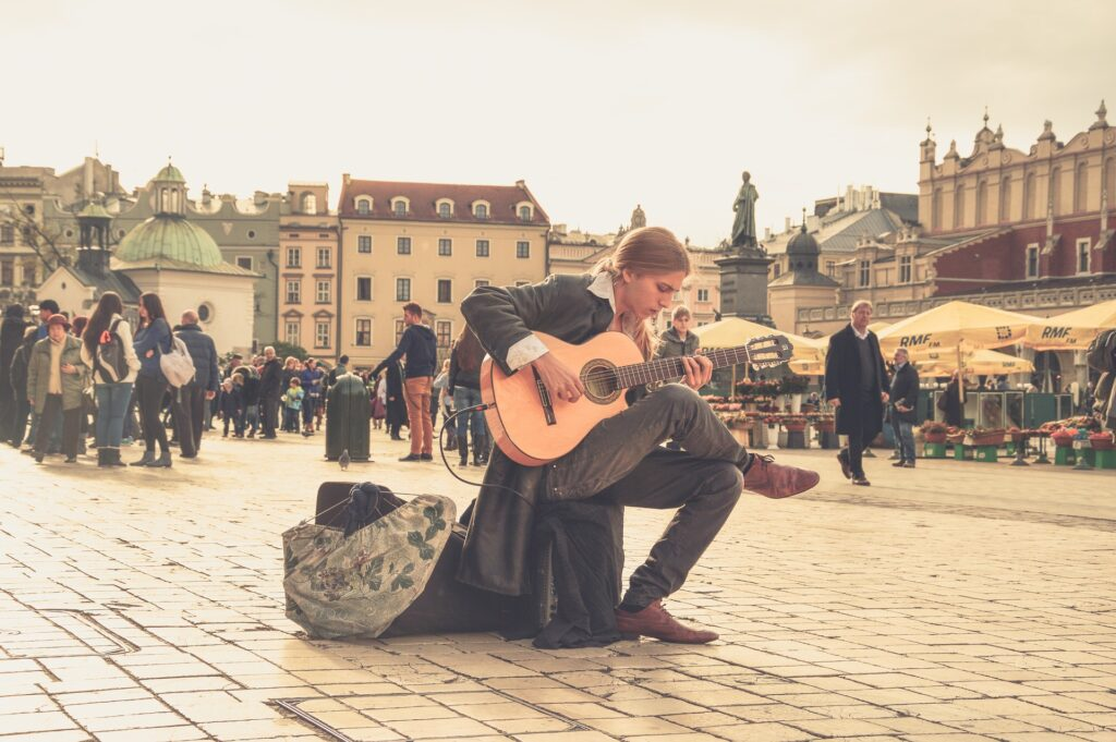 man busking in european square with acoustic guitar