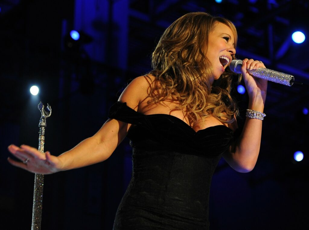 singer in black dress belting out on microphone