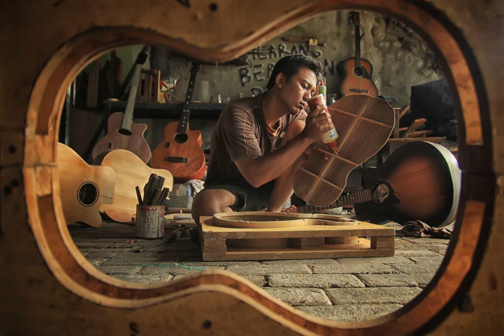 man building a guitar seen through the outline of a guitar body