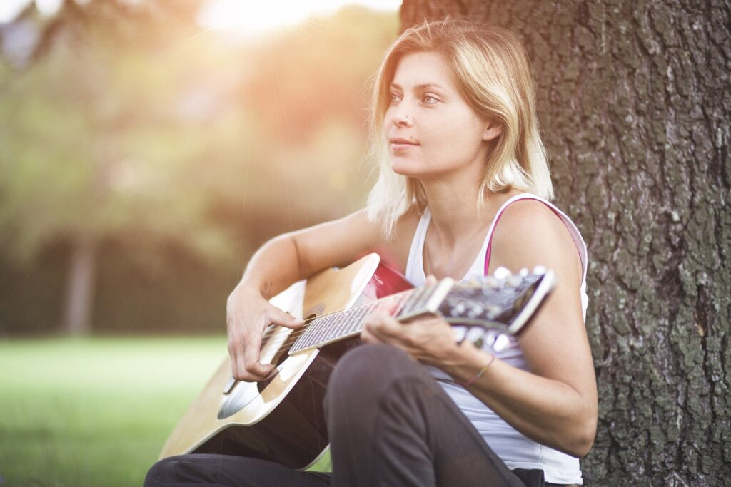 Girl playing guitar by tree